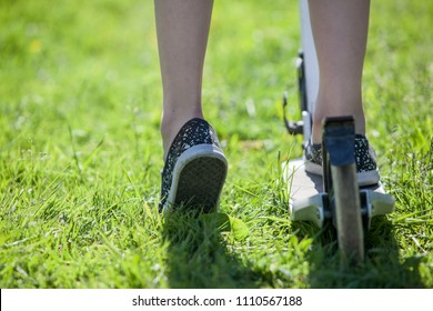 Two casters-rollers cycle and Caucasian children feet riding on green grass
