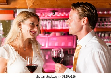 Two (casual) business people in a hotel bar in the evening having glasses of red wine and a little flirt