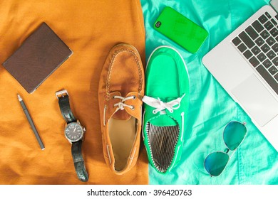 Two casual shoes of different colors bordered with colors and surrounded by laptop keyboard, mobile phone, watches, glasses, pen and notebook. Light orange and turquoise version. Top view. Flat lay.
