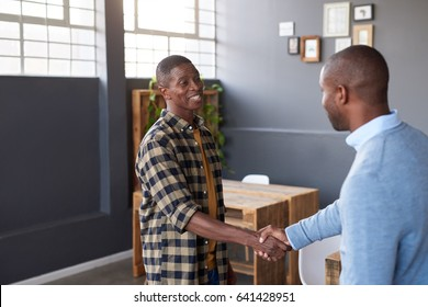 Two casually dressed young African business colleagues smiling and shaking hands together while standing in a large modern office