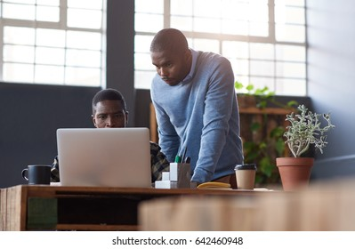 Two casually dressed young African business colleagues talking together over a laptop while working at a table in a modern office