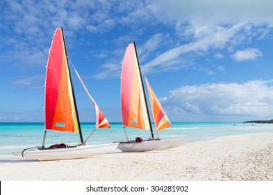Two catamarans with its colorful sails wide open on Cuban white sandy beach, Cayo Santa Maria