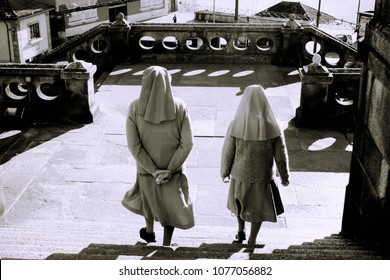 Two catholic nuns go down the stairs of a church in Porto, Portugal.