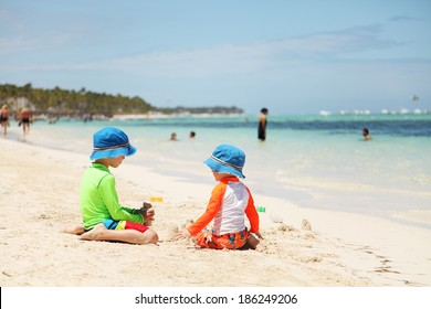 Two caucasian boys playing with sand at tropical beach