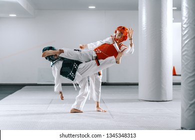 Two Caucasian boys in taekwondo fittings kicking and fighting at training.