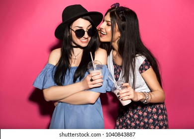 Two caucasian brunette hipster woman in casual stylish outfit having fun drinking milkshakes with straws. They standing on a bright pink background. They gossip with a cheerful, happy emotions