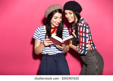 Two caucasian brunette hipster woman in casual stylish french outfit with beret, having fun reading books, smiling. They standing on a bright pink background. Cheerful, happy emotions