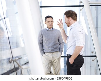 two caucasian business people having a casual conversation by the window in modern office building.
