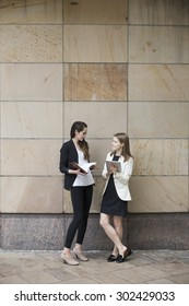 Two Caucasian Business women using digital tablet computer, leaning against a wall.