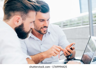 Two caucasian businessmen using smartphone outdoors - Two professional businessmen working outdoor using smartphone - business, technology, communication concept
