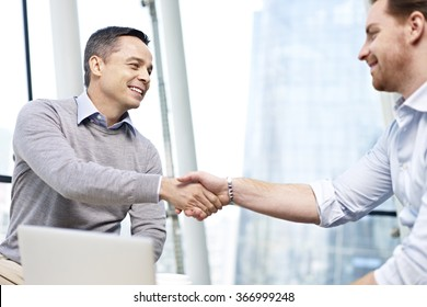 two caucasian businesspeople smiling and shaking hands in office.