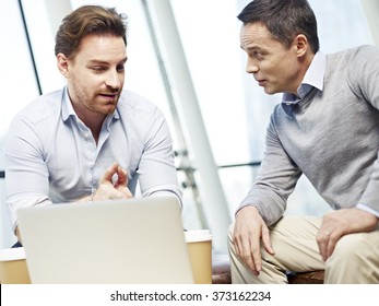 two caucasian corporate executives in casual wear having a business discussion in office.