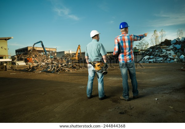 two caucasian engineers standing in recycling center outdoors, pointing at pile of scrap metal