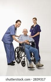 Two Caucasian females wearing scrubs with elderly Caucasian male in wheelchair.