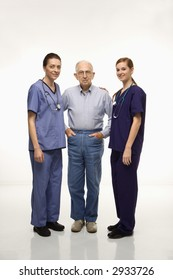 Two Caucasian females wearing scrubs standing with elderly Caucasian male.