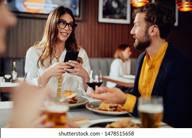 Two Caucasian friends dressed smart casual having dinner and chatting while sitting in restautrant.
