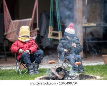 Two caucasian little boys in winter dress grilling sausages on sticks in the garden. Traditional Slovak barbecue. Family activity during lock down.