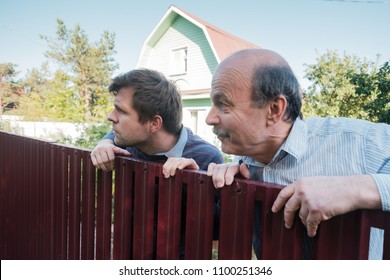two caucasian men carefully watching over the fence. Concept of curious neighbors and private life