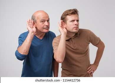 Two caucasian men hearing with hand on ear isolated on a white background. Please speak loudly. Having problem with hearing