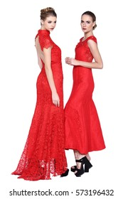 Two Caucasian Models in Red Lace Long evening ball gown Dress, chinese qipao style in high heels, concept of mother, dauther, sisters, close friends and lovers, isolated on studio lighting white