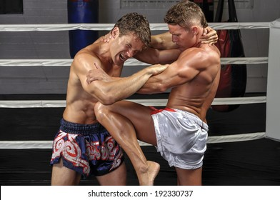 Two Caucasian Muay Thai fighters lock up in the ring during match and one delivers powerful knee to the mid-section
