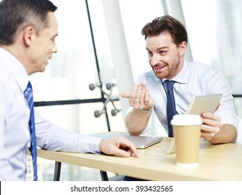 two caucasian office people discussing business using tablet computer in office.