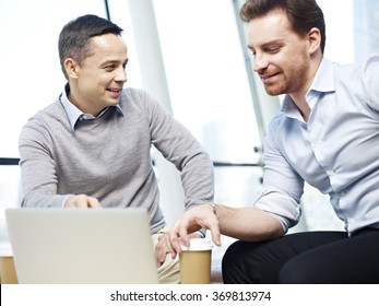 two caucasian office workers in casual wear discussing business in office.