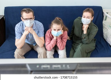 Two Caucasian parents with teenager daughter in medical masks sitting behind tv set on sofa in living room, people tired to watch television