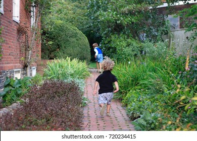Two Caucasian toddler boys running on a brick path in a garden.