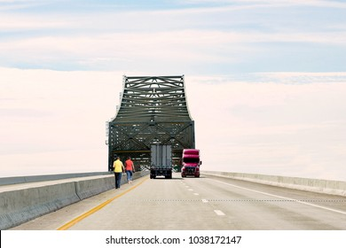 two caucasian weman walking along the side of the freeway under a tall concrete bridge with semi trucks driving at high speed.