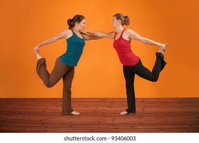 Two Caucasian women perform yogasana over orange background