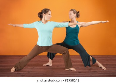 Two Caucasian women practicing yoga stretch their legs