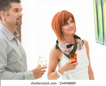 two caucasian young people standing and holding colorful wine glasses, looking at paintings displayed on white walls