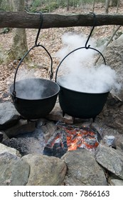 two cauldrons over an open fire in an historical setting