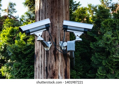 Two cctv security cameras on a pole in daylight