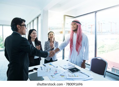 Two CEO between Asian and Arabs people, shaking hands after agree business deal  and staff clapping congratulation for the success.