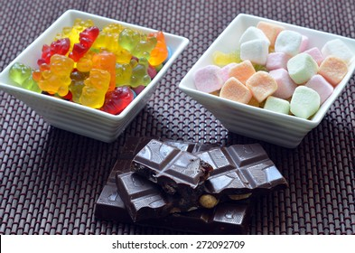 Two ceramic bowls of colored smarties, sour candies, chocolate and gummy bears on bamboo wooden pad