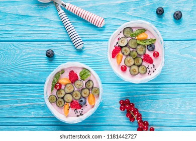 Two ceramic bowls with whipped quark mousse, raspberries, blueberries, red currant and fizalis on a blue background. Top view, free space