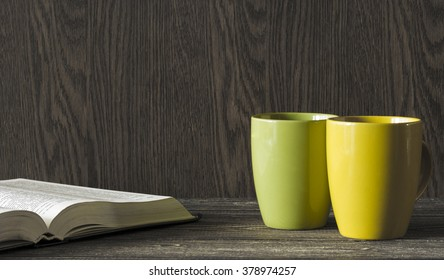 Two ceramic mugs yellow and green stand in the corner of a wooden table in front of an open book. Darkened