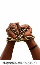 Two chained black male hands of a young South African Xhosa imprisoned man. Image isolated on white studio background.