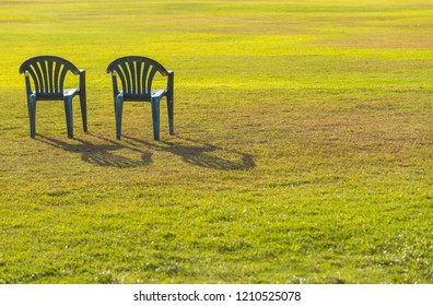 Two chairs on green lawn at sunset