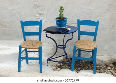 Two chairs outside a Greek restaurant, in te traditional blue and white color scheme