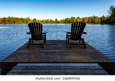 Two Chairs sitting on a wood dock facing a lake in a calm autumn season sunny day