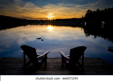 Two  chairs sitting on a wood dock facing a calm lake at sunset. Across the water are cottages nestled among trees. The season is summer.
