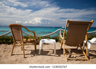 Two chairs and a small table on the sand of a beach in front of a seascape and under an expressive cloudy sky.