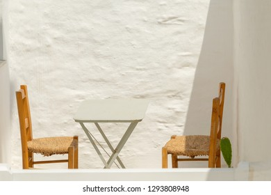 Two chairs and a table. Retro scenic at Andros island in Greece.