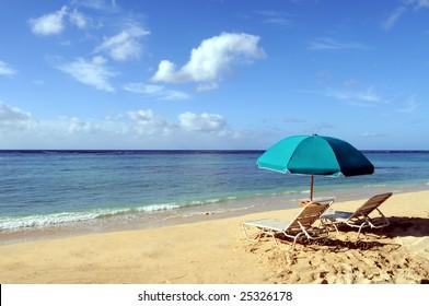 Two chairs and an umbrella on the beach in Waikiki Beach, Honolulu, Hawaii