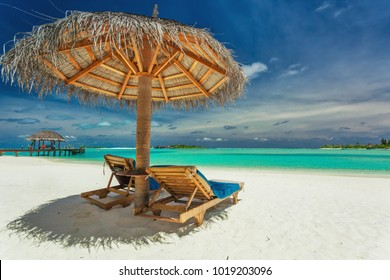 Two chairs and umbrella on stunning tropical beach in Maldives