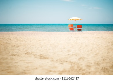 Two Chairs and Umbrella at sandy beach in Durres, Adriatic Sea shore of Albania