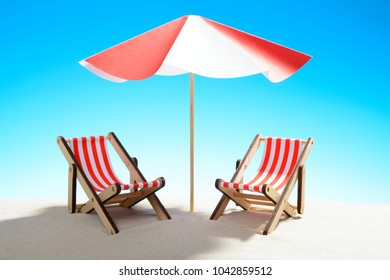 Two chaise longue under an umbrella on the sandy beach, sky with copy space